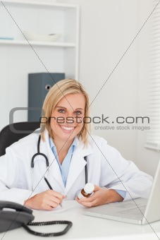 Doctor writing something down while holding medicine looks into