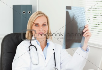 Charming doctor holding x-ray looks into camera