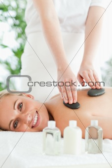 Blonde relaxed woman experiencing a stone therapy