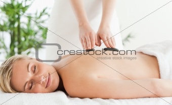 Blonde relaxed woman experiencing a stone therapy with closed ey