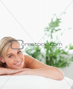 Close up of a blonde smiling woman lying on a lounger