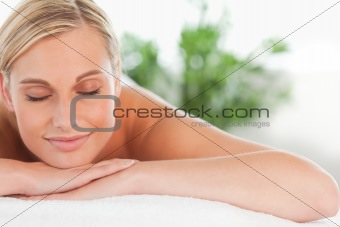 Close up of a blonde smiling woman relaxing on a lounger with ey