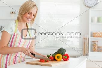 Cute woman cutting red pepper