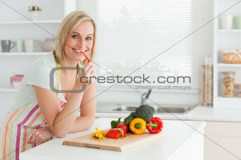 Portrait of a woman eating red peppers