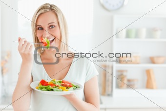 Close up of a charming woman enjoying mixed salad