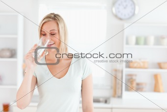 Charming woman drinking waterwhile standing