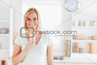 Charming woman holding glass filled with water while standing