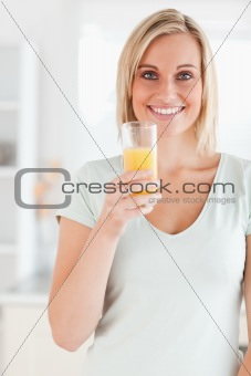 Charming woman holding glass filled with orange juice