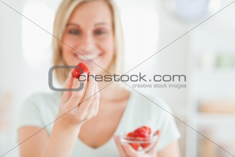 Close up of a young woman enjoying eating strawberries