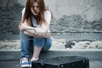 Beautiful young sad girl sitting on asphalt. Photo in cold tones