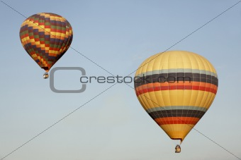 Two multi-colored balloons blue sky