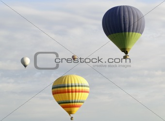 four colorful balloons cloudy sky