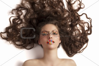 beautiful model laying on white wearing candy make up