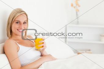 Blonde woman drinking orange juice