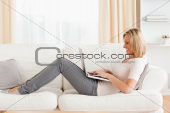 Cute woman using a laptop while lying on a sofa