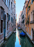 Narrow channel in venice with some boats at dawn