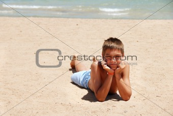 Boy lying on the beach