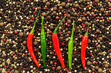 Red and green peppers on pepper background
