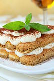 Traditional Italian dessert tiramisu on white plate