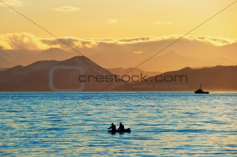 Fishermen by a boat in an evening bay