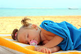 little girl sleeping on beach