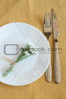Fork, knife, plate and small white flowers