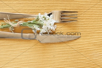 Fork, knife and a small bouquet of white flowers