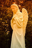 Statue of crying angel in sunset rays