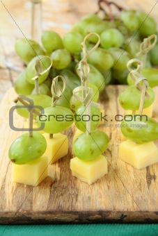 appetizer canape cheese with white grapes on bamboo skewers