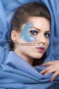 model laying on purple silk sheets