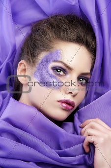 young girl laying on purple fabric wearing glitter make up