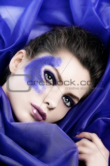 beautiful girl in the middle of purple fabric
