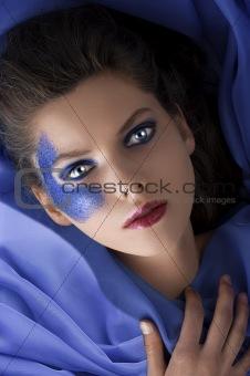 beautiful girl laying between blue satin sheets