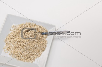 Bowl of dry oat flakes with spoon