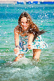 Beautiful young girl splashing the water in the sea