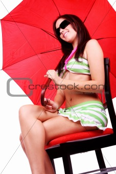 Beautiful young woman on a bathing suit sitting holding a red um