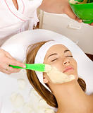 young woman getting beauty skin mask treatment on her face 