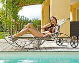 Sexy young woman relaxing on deck chair