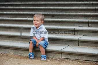 little boy sits on on the stairs in a park