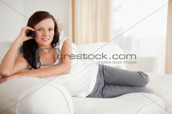 Smiling woman on the phone relaxing on a sofa
