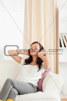 Beautiful red-haired woman listening to music on the sofa