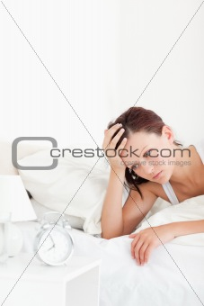 Close up of a tired red-haired woman waking up