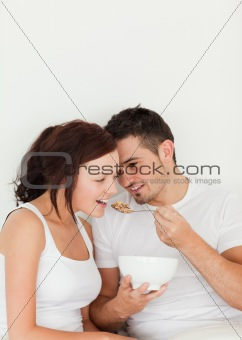 Close up of a man feeding cereal to his wife