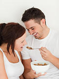 Portrait of a man feeding cereal to his wife