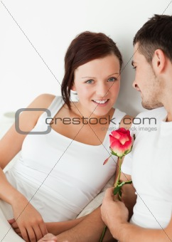Close up of a Cheerful couple with a rose looking into camera