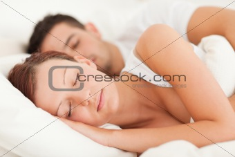 Sleeping couple lying in their bed