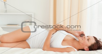Close up of a gorgeous Woman phoning on her bed