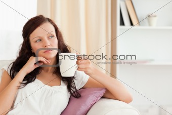 Thoughtful woman holding a cup