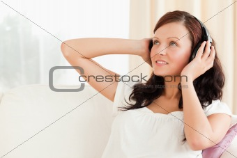 Cute woman relaxing with music on her sofa