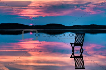 Chair in calm water with sunset